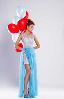 Wwoman wearing beautiful dress with a lot of colorful balloons