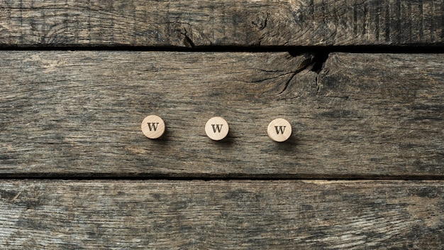 Www sign spelled on three wooden cut circles placed on rustic wooden boards.