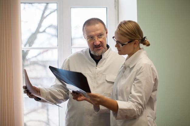 X線画像を分析する2人の医師