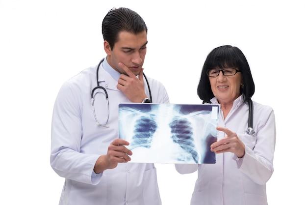 白で隔離されるx線画像を見ている2人の医者