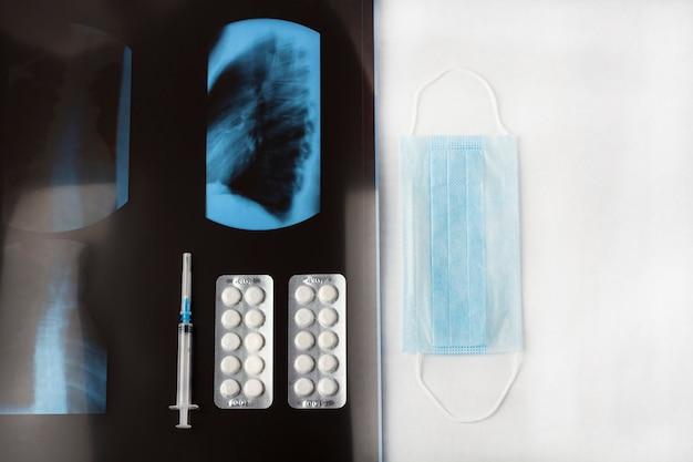 肺、薬、白い背景の上の注射器のx線フィルムで保護医療フェイスマスク。治療症状コロナウイルス、covid-19、肺炎および気管支炎の概念。