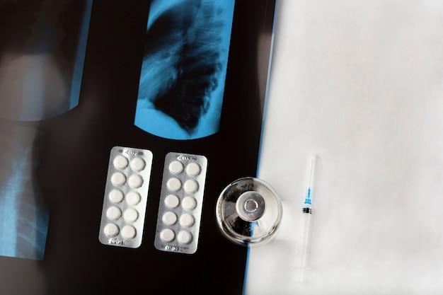 肺、薬、注射器、ワクチン瓶のx線フィルムが貼られた保護用医療用フェイスマスク。治療症状コロナウイルス、covid-19、肺炎および気管支炎の概念。