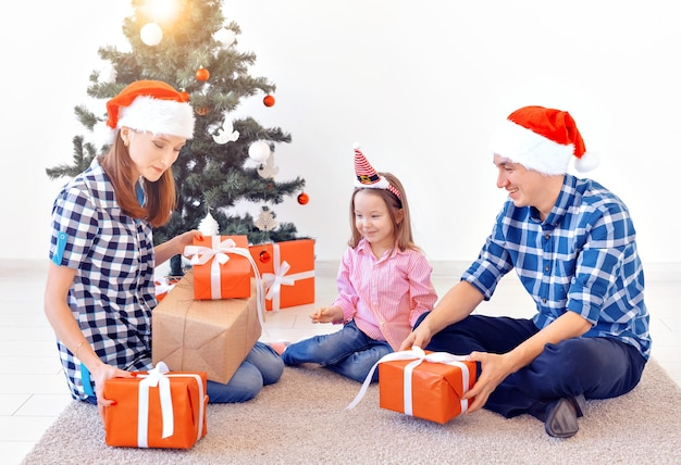 X-masと休日のコンセプト-木の前でクリスマスプレゼントを開く家族。