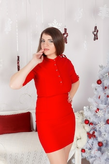 X-mas, winter, holidays and people concept - happy young woman decorating christmas tree at home