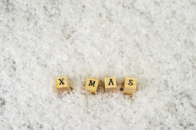 X mas word made of letters on wooden cubes on a snow
