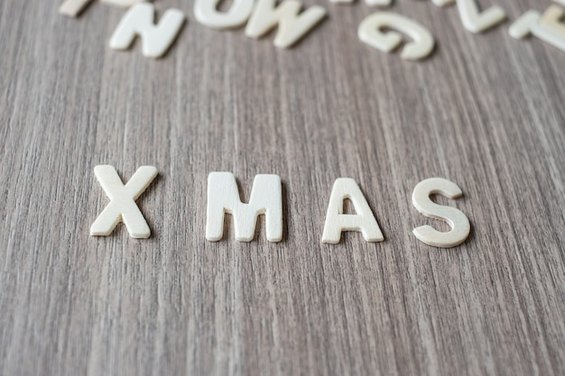 木製のアルファベットのx masワード。メリークリスマス、そしてハッピーニューイヤー