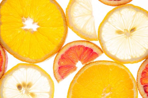 과일의 엑스레이. 루멘 배경에 감귤류 과일 오렌지와 레몬의 다른 조각. 상위 뷰 및 매크로