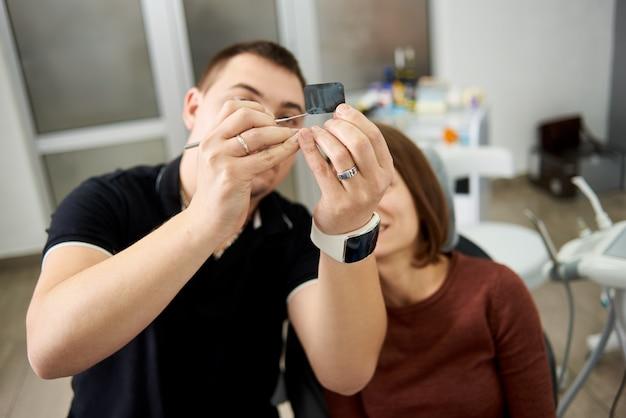 歯科医は、現代の歯科医院で撮影された歯のx線写真の特徴を患者に示します。 x線写真に焦点を当てる