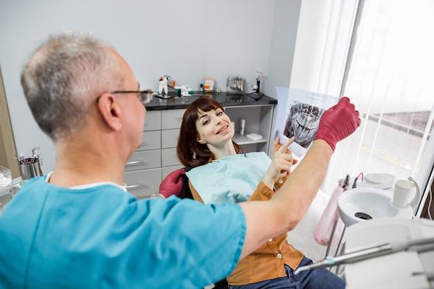 歯のx線画像を保持しながら、メスの患者と話し、治療の準備をする歯科医院のシニア男性歯科医。彼女の歯科医とx線画像を見て歯科医院の女性