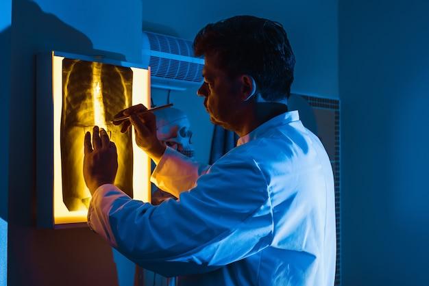 医者はネオンの光の中で肺のx線を検査します