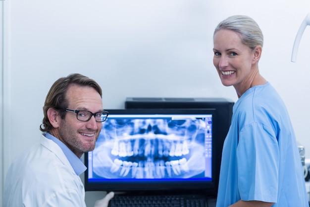 モニターでx線について話し合う歯科医と歯科助手