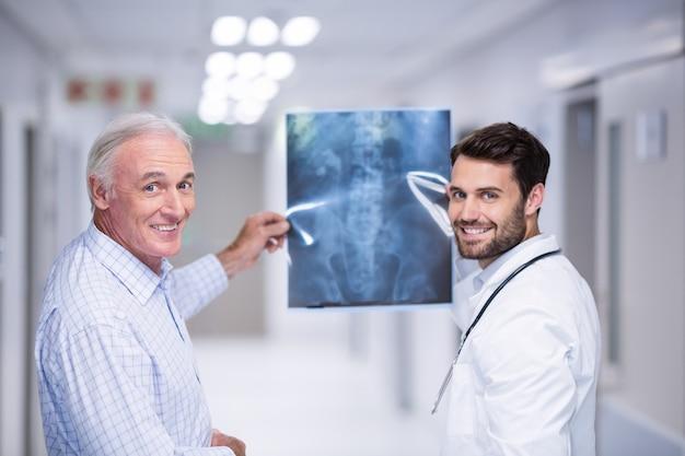 医師と廊下でx線を保持している患者の肖像画