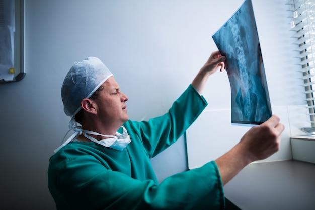 外科医が窓際に座ってx線をチェック