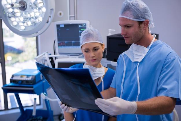 男性と女性の看護師が手術室でx線を調べる