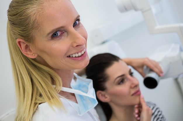 歯科医は女性患者の歯のx線を撮影