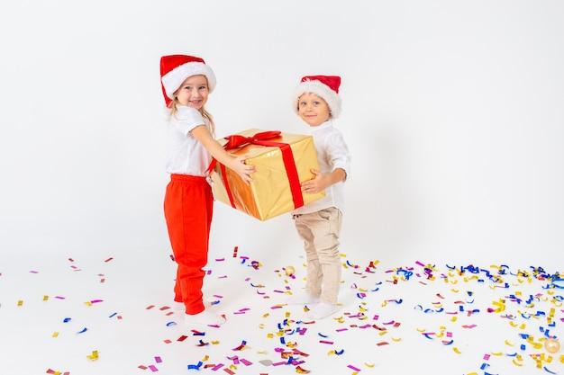 大きなギフトボックスを保持しているサンタ帽子で幸せな小さな子供たち。白い壁に分離されました。販売、休日、クリスマス、新年、xマスの概念。