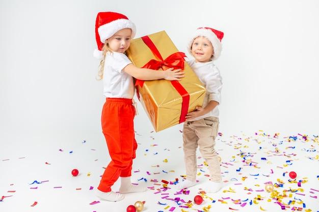 大きなギフトボックスを保持しているサンタ帽子で幸せな小さな子供たち。白い背景に分離します。販売、休日、クリスマス、新年、xマスの概念。