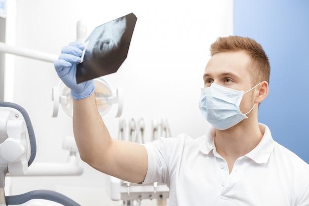 プロの男性歯科医が歯のx線を調べる