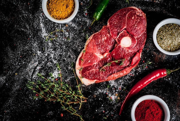 新鮮な生肉。古いさびた黒の金属製のテーブルで調理するためのスパイスと骨、カッティングx、子羊のテンダーロインの一部トップビュー