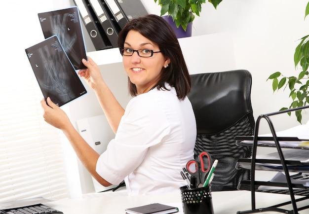 女性医師は壊れた手のx線を見ています。