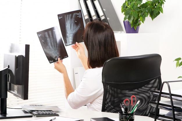 若い女性医師はx線を見ています。