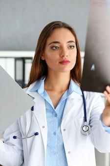 美しい女性医師が腕のx線写真を保持します。
