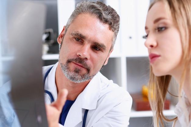 成熟した男性医師が腕を抱えてx線写真を見て