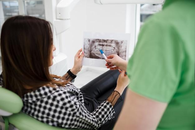 歯科医師は彼の患者に口腔のx線を表示します