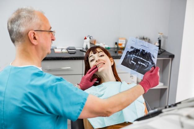 歯のx線画像を保持しながら、メスの患者と話し、治療の準備をする歯科医院のシニア男性歯科医