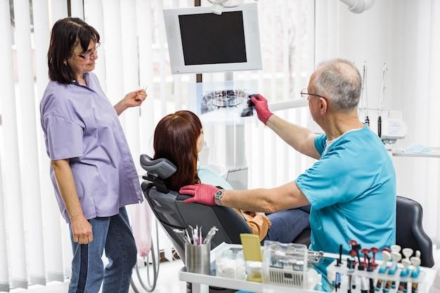 歯科医のチーム、年配の男性歯科医と彼の女性アシスタント、歯科医院で女性患者と話しているとx線画像の検査中の治療の準備