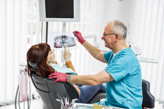 若い女の子の患者と話していると治療の準備の歯科医院でシニア男性歯科医。 x線画像の検査。