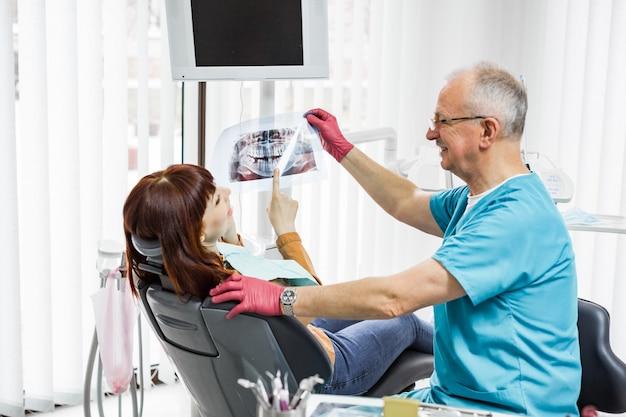 現代の歯科医院の歯科用椅子に座っている若い女性患者に歯科用x線を示すプロのシニア男性歯科医の笑顔