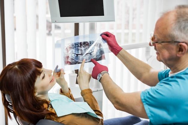 彼の美しい魅力的な女性患者と一緒に歯科用x線を見てハンサムなシニア男性医師歯科医