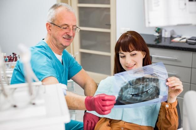 彼の若い笑顔の女性患者のx線画像を見てハンサムな年配の男性歯科医。