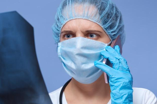 彼女の同僚と電話で話している患者のx線を調べるショックを受けた女性医師