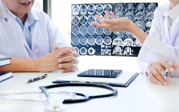 医師がコンサルティングルームのx線フィルムでコンサルタントを説明する