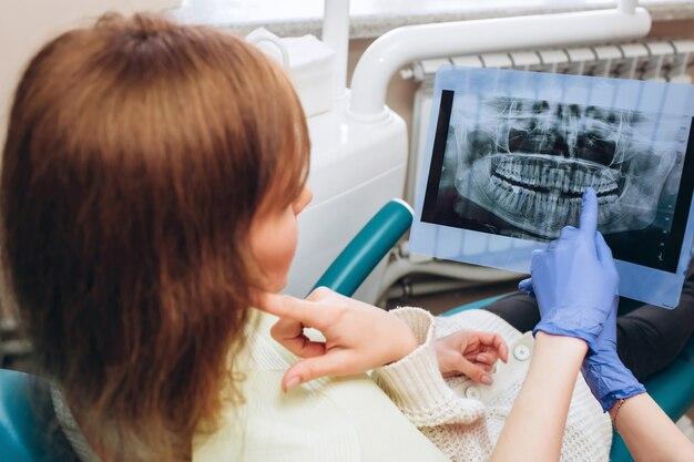 家族の家の歯科医はx線を示しています。歯科医の近くの受付に座っている若い女性。少女歯科医