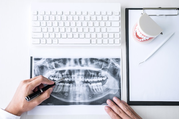 患者の歯のx線フィルム、モデルと治療に使用される機器を扱う医師または歯科医