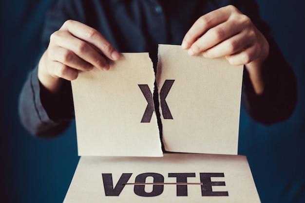 Человек рвет коричневую бумагу с отметкой x над клеткой для голосования