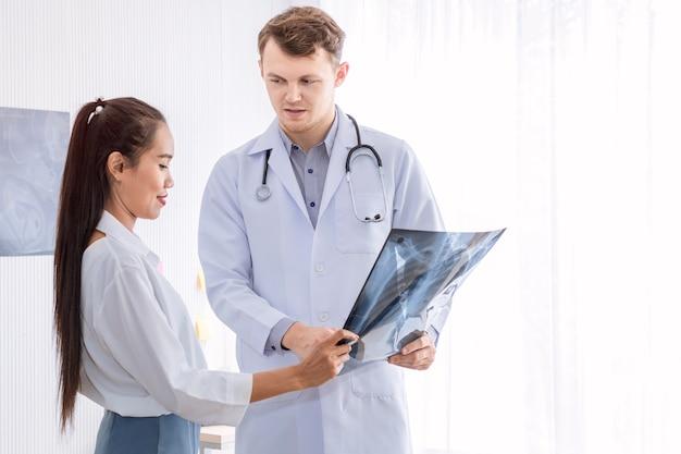 医療専門家白人男性がx線を押しながら患者と会話します。