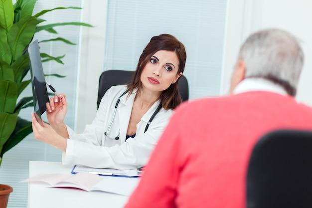 医者は彼女の患者とx線撮影を調べる