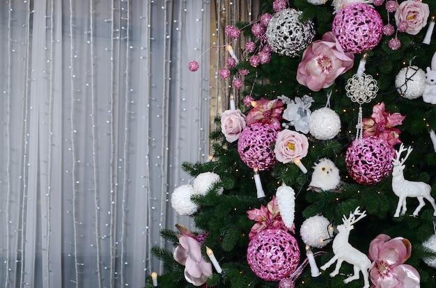 クリスマスツリーを飾ることをクローズアップ。装飾用電球、モミの木、ピンクのxマスおもちゃ、ライト