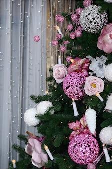 クリスマスツリーを飾ることをクローズアップ。装飾電球、モミの木、ピンクのxマスおもちゃとライト