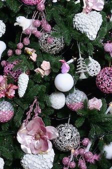 クリスマスツリーを飾ることをクローズアップ。装飾電球、モミの木、ピンクのxマスのおもちゃとライト。クリスマスや新年のお祝いに使用