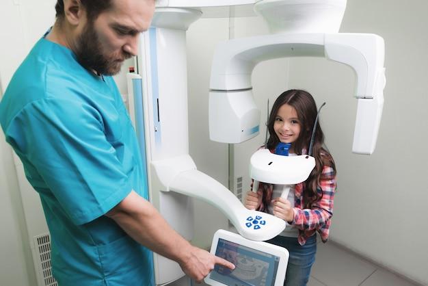男性医師が少女の顎のx線を撮影します。