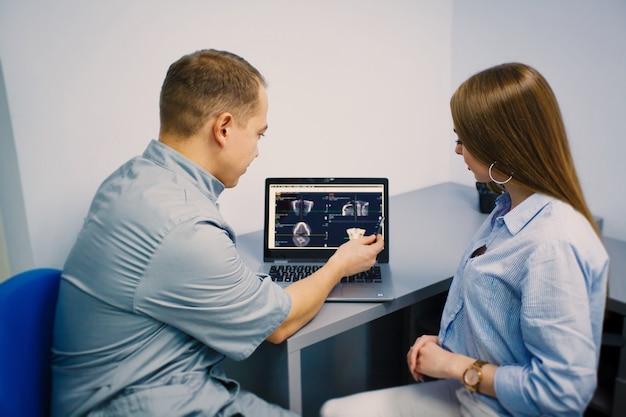 歯医者は患者に自分の歯のx線写真をコンピューターモニターで見せる。