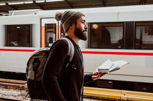 Привлекательный молодой человек с бородой ждет на вокзале в вене. думая о поездке, с картой в руке и рюкзаком. туристическая фотография.