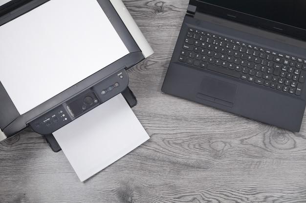 Xeroxプリンターマシン、ラップトップ、机の上の紙。