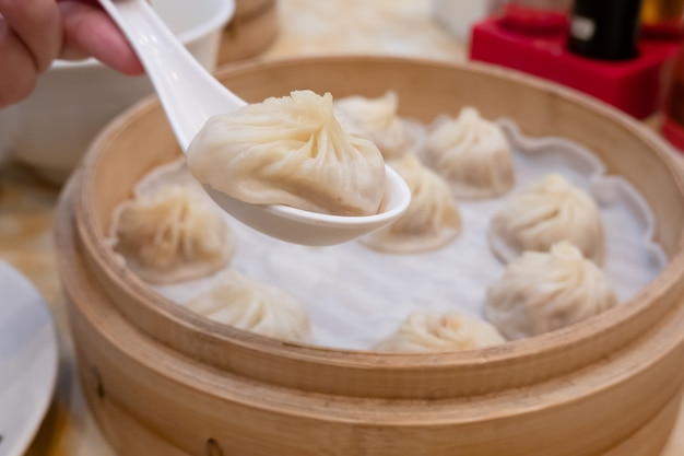 Xiao long bao soup dumpling buns with chopsticks in restaurant (traditional chinese food)