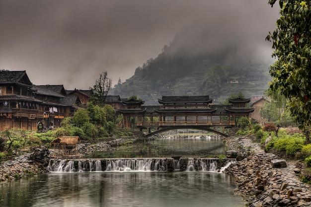 中国貴州省西江ミャオ族の村朝の霧の中のミャオ族の少数民族の村、木造家屋、田舎の川に架かる屋根付きの彫刻が施された橋。